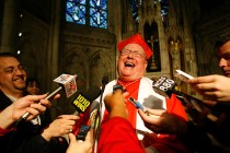 Cardinal Timothy Dolan laughs with reporters after holding a prayer service